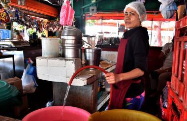 Una comerciante recolecta agua en La Ciudadela.