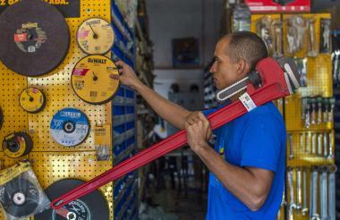 Andrés Henríquez acomoda unas herramientas en la tornillería donde labora.
