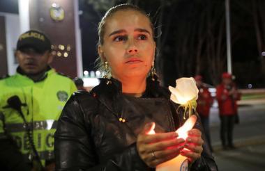 Un familiar de una  víctima carga una vela a las afueras de la Escuela de Cadetes de Bogotá.