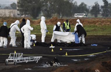 Autoridades en labores de levantamiento de cadáveres en la zona de la explosión de la red de combustible.