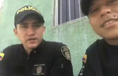 Dos agentes de la Policía en momentos que realizan la dedicatoria a los compañeros fallecidos en atentado.