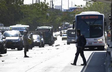 Un peatón sale de la estación y se atraviesa al paso de  un bus articulado y un alimentador.