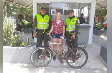 La ciudadana extranjera junto con los policías que recuperaron su bicicleta.