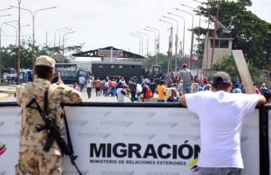 Un soldado colombiano observa  los dos camiones del Ejército venezolano, al fondo, en el paso fronterizo.