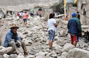 Un hombre se sienta en una roca mientras los residentes caminan entre los escombros el día después de un deslizamiento de tierra provocado por fuertes lluvias, que afectó a la aldea rural de Aplao, región de Arequipa, Perú.
