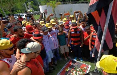 Aficionados y familiares de las víctimas del incendio llloran a la entrada del club Flamengo.