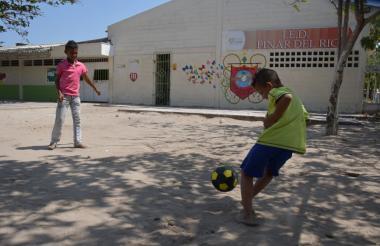 Niños juegan fútbol mientras esperan inicio de clases.