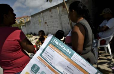 Usuarios del servicio de energía en el barrio Edén de Barranquilla muestran el registro de la factura.