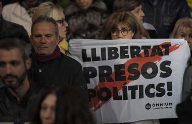 """Mujer sostiene un cartel  que dice """"presos políticos libres"""" durante manifestación en Barcelona."""