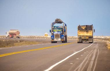 Dos vehículos de carga transitan por el kilómetro 19 de la vía.