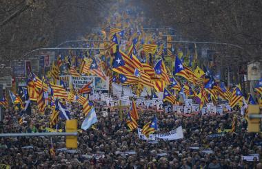 Cientos de personas marchan en protesta contra el juicio de exlíderes separatistas catalanes en Barcelona.