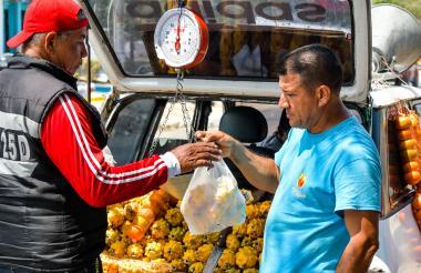 Osvaldo Mujica (derecha) le entrega a Catalino Pérez las frutas que le vendió.