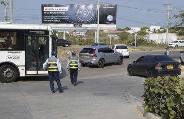 Tres agentes de tránsito guían el tráfico en el corredor universitario.