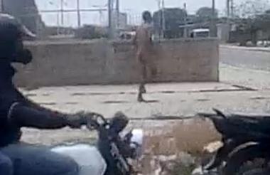 El hombre corre desnudo en la calle.