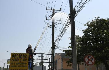 Un funcionario realiza el lavado de redes eléctricas de un sector de Barranquilla.