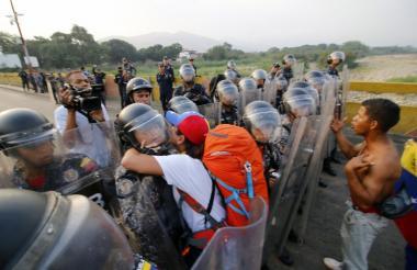 Un hombre abraza a un miembro de la Guardia Venezolana mientras otro reclama el paso hacia Colombia. La frontera fue cerrada este viernes por orden del gobierno de Maduro.