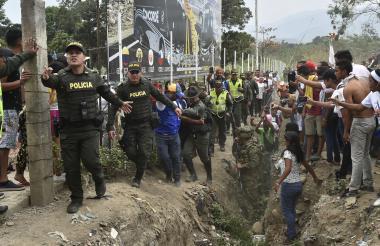 Miembros de la Policía Nacional conducen a un miembro de la Guardia Bolivariana (cubierto) que desertó a través de Cúcuta.