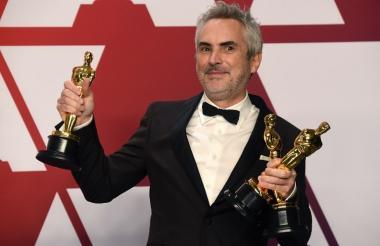 Alfonso Cuarón, director de cine mexicano, con las tres estatuillas obtenidas.