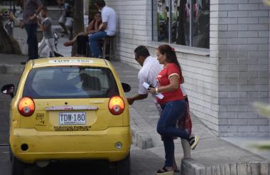 Usuarios de taxis negociando el valor de la carrera por el servicio.