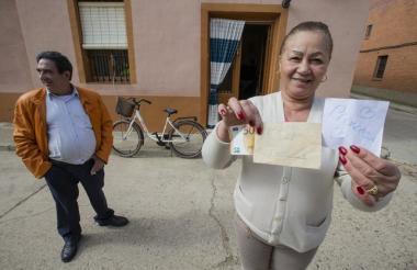 Una mujer muestra el dinero que recibió en los sobres en su casa.