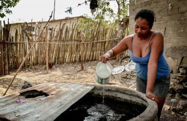 Una ama de casa recoge agua de la alberca de su patio en el corregimiento de Gallego, Sabanalarga, en el Atlántico.