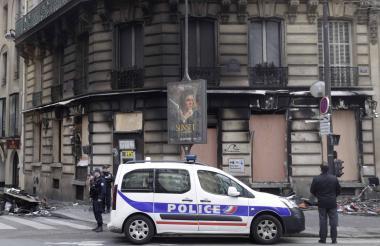 Policías custodian un banco quemado en París.