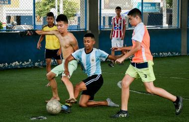 Un grupo de menores juegan fútbol en una de las canchas del bulevar de Simón Bolívar.