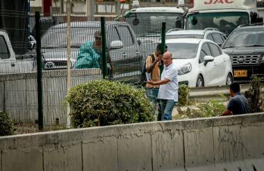 Dos personas se apoyan de la malla para buscar una zona por donde cruzar la Circunvalar, pese al riesgo.