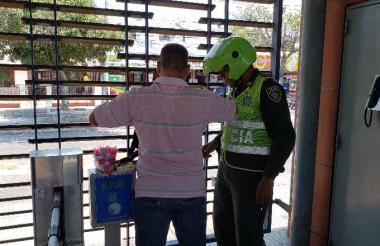 Un policía insta a un vendedor a salir de la estación.