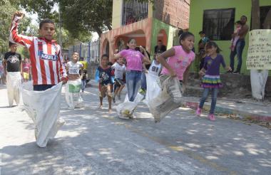 Niños jugando a carreras de saco en el barrio 7 de Abril, durante la celebración del cumpleaños.