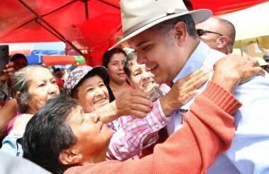 Duque es abrazado por una habitante de Timbío (Cauca) a su arribo a esta población caucana.