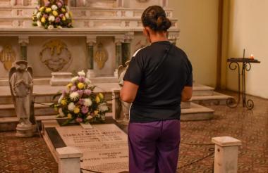 Amanda Pérez reza frente a la tumba del padre Matutis, ubicada en la iglesia San Roque.