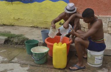 Habitantes recogen agua en pimpinas.