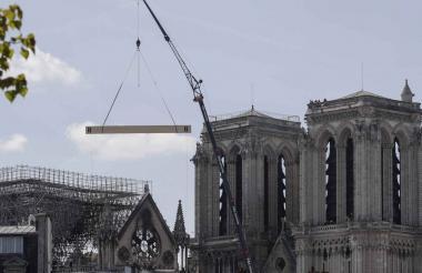 Una grúa levanta material de construcción mientras los andamios rodean la catedral de Notre-Dame.