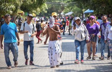 Un penitente recorre la calle de la Ciénaga, en Santo Tomás, mientras se flagela con bolas de cera ante la mirada de sus familiares y espectadores.