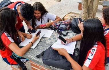 Alumnos de la Escuela Normal La Hacienda estudian con la ayuda de sus celulares, durante su receso.
