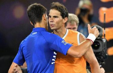 Djokovic y Nadal se abrazan al término de la final del Abierto de Australia.