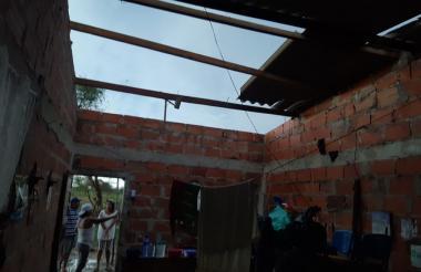 Una familia observa el daño causado por la lluvia que cayó este viernes en Puerto Giraldo.