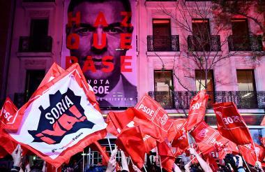 Personas ondean banderas del PSOE, celebrando la victoria de Pedro Sanchéz en las elecciones.