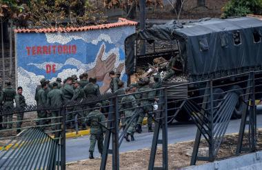 Miembros de la Guardia Nacional  limpian las piedras y los escombros en la base militar La Carlota.