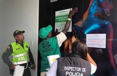 Un uniformado, un funcionario de Espacio Público y un inspector realizan el cierre de un bar en la calle 82.