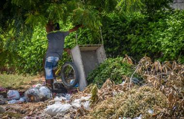 Un  reciclador vacía la basura que tenía en su carretilla.