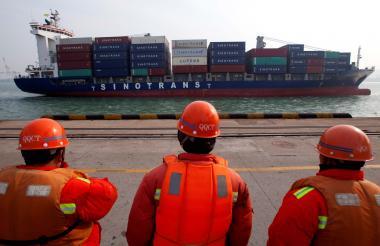 Trabajadores observan un barco  de la compañía china Sinotrans Shipping Ltd.