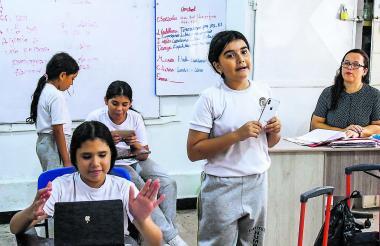 Dos estudiantes exponen con sus aparatos electrónicos, ante la mirada de la docente.