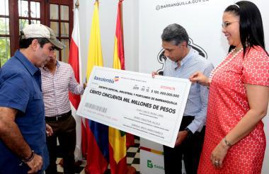 El alcalde Char y la secretaria Emelith Barraza reciben el cheque por parte de funcionarios del banco.