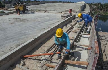 Dos obreros adecúan la acera del puente que atraviesa el Caño de Las Compañías.