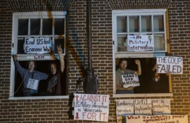 Activistas en contra de Nicolás Maduro se asoman en las ventanas de la embajada de Venezuela en Washington.