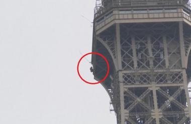 Hombre escalando la Torre Eiffel.