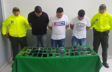 Los tres capturados con los celulares incautados.