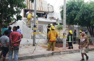 Un bombero ayuda a una de las residentes de la vivienda a bajar del segundo piso.